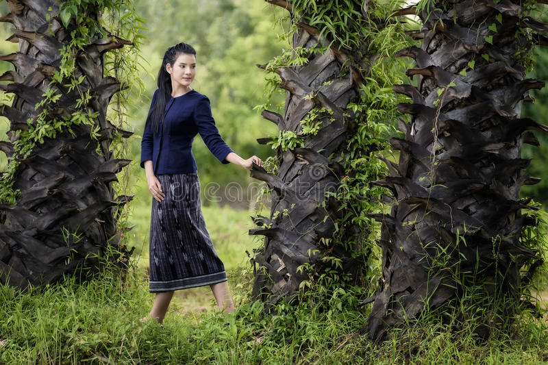 Thai woman in the countryside traditional costume portrait under the sugar palm trees row. Thailand stock photo