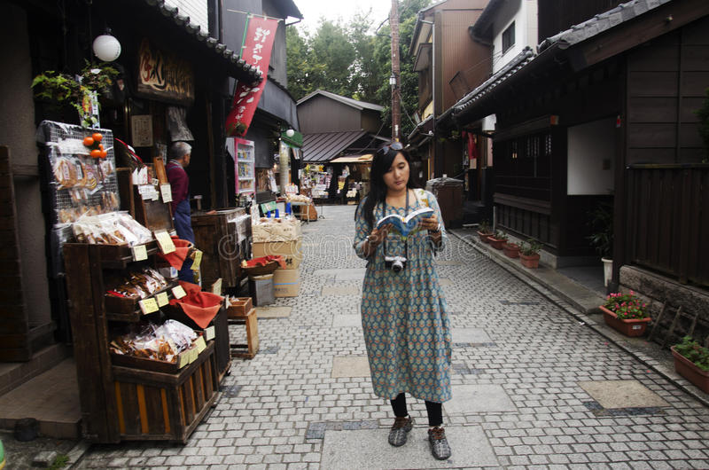 Thai woman reading guide book and visit snack and candy alley japanese style called Kashiya Yokocho at Kawagoe town or Little Edo royalty free stock image