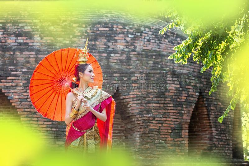 Thai Woman In Traditional Costume with umbrella of Thailand. Female  Traditional Costume with thai style temple background. Wat stock image