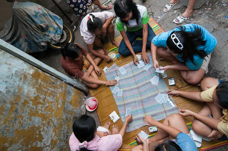 Thai women play money on cards in the slum of KLong Toey in Bangkok. Money games are prohibited in Thailand. royalty free stock photo