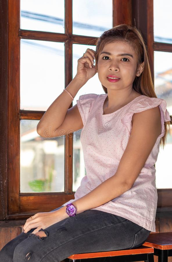 Thai women sitting near wooden window lighting stock images