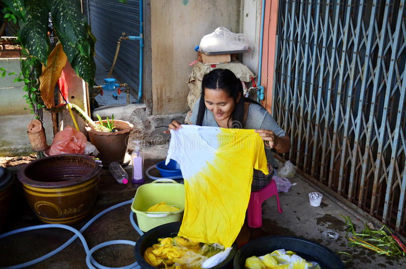 Thai women washing and clean clothes after tie batik dyeing natural color. Thai woman washing and clean clothes after tie batik dyeing natural color at royalty free stock photo