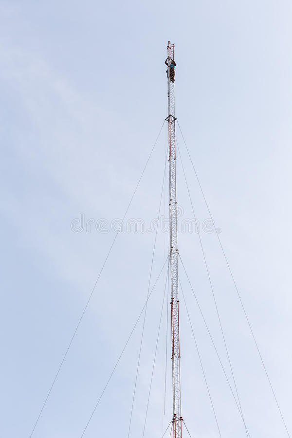 Thai worker is working on high communication tower royalty free stock photos