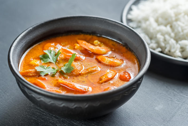 Thai yellow curry with seafood and white rice. Bowl of thai yellow curry with seafood and white rice on the dark background stock image