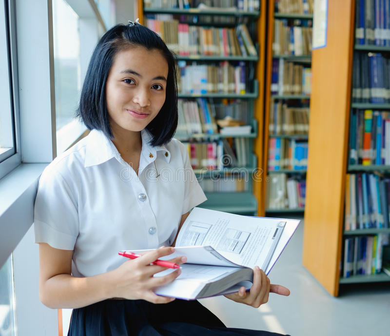 Thai young woman student reading a book stock image