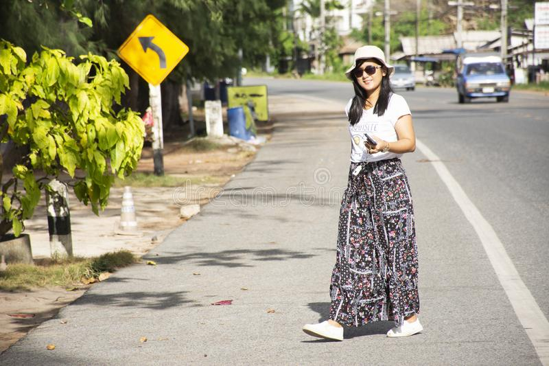 Thailändische Frau der Reisenden, die neben Straße nachher über Verbot Phe-Straße in Rayong, Thailand geht stockbilder