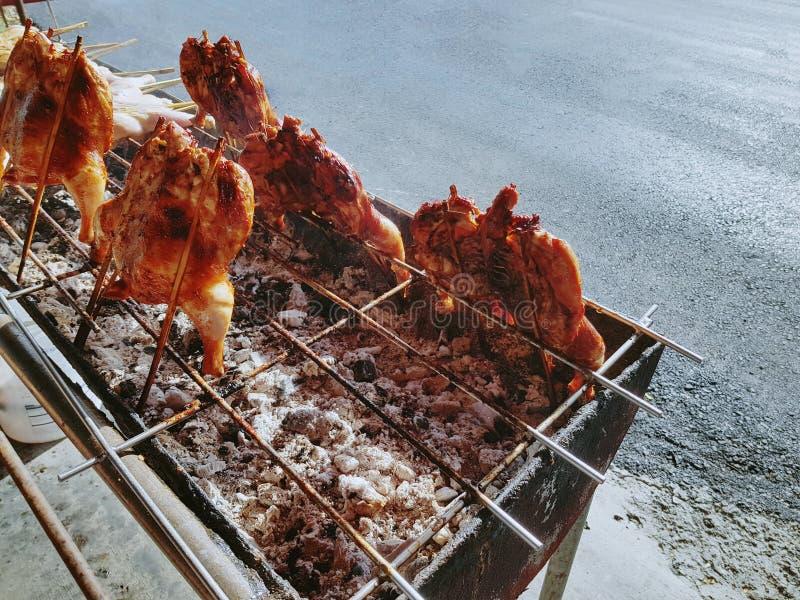 Thailändisch-ähnliche Straßen-Nahrung Gegrillte würzige Hühner auf kleinem Ofen stockfotos