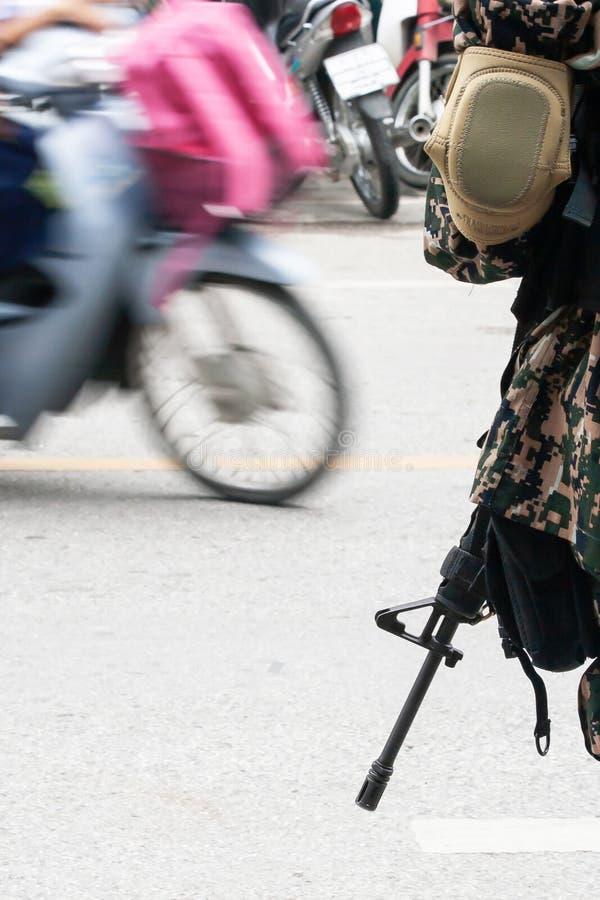 Thail?ndische Armee mit Gewehr in seiner Hand w?hrend der Sicherheitspatrouille nahe einem lokalen Markt in Narathiwat, S?d-Thail lizenzfreie stockfotos