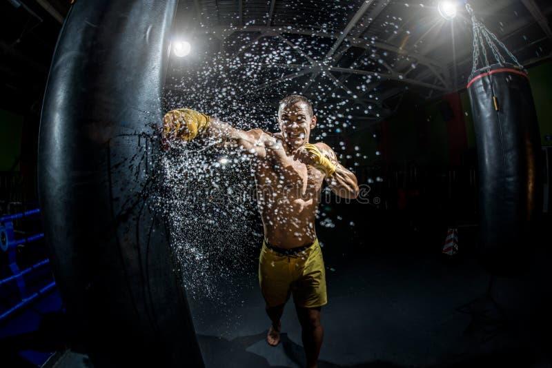Thailändische Boxerdurchschlagshand durch Sandsack stockfotos