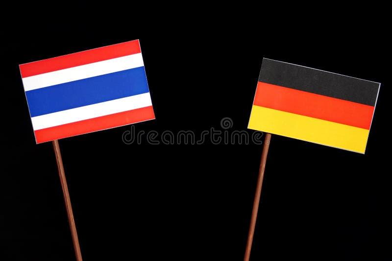 Thailändische Flagge mit deutscher Flagge auf Schwarzem lizenzfreie stockfotografie