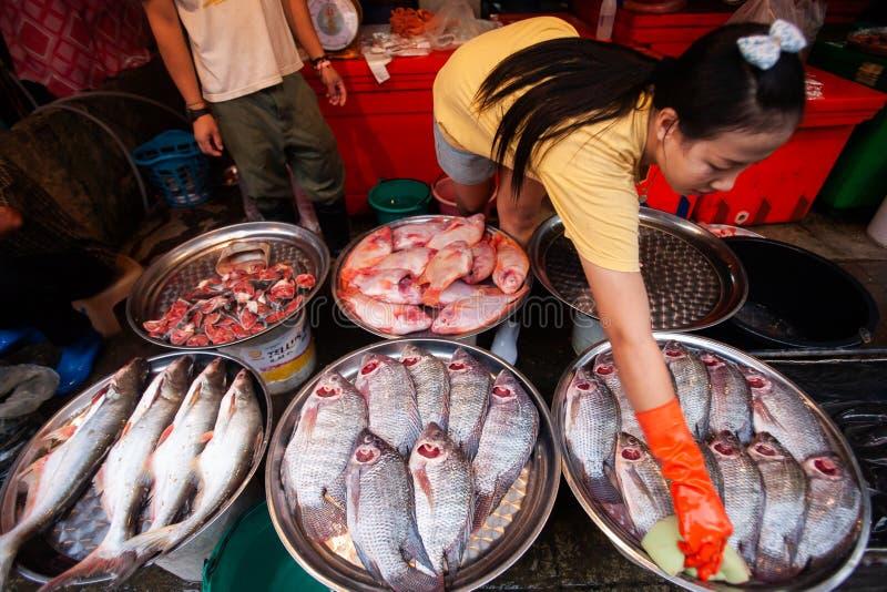 Thailändische Frau des Verkäufers mit den Latexhandschuhen, die Frischwasserfische an säubern stockfotografie