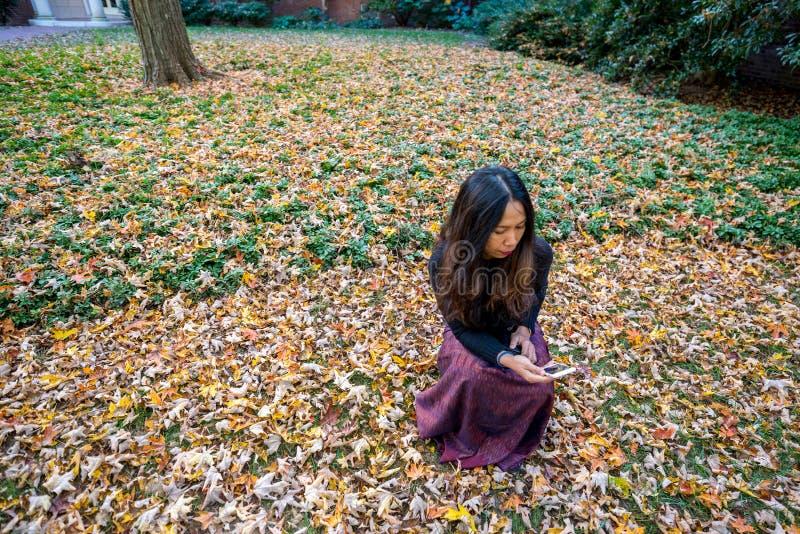 Thailändische Frau, die auf dem Boden umgeben durch Blätter im Fall L knit lizenzfreie stockfotos