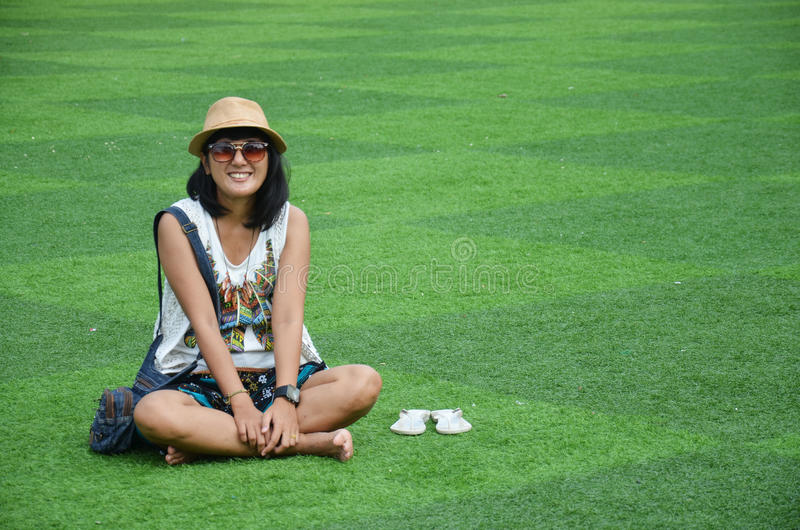Thailändische Frau, die auf künstlichem Rasen am Garten in Kanchanaburi Thailand sitzt lizenzfreie stockfotografie