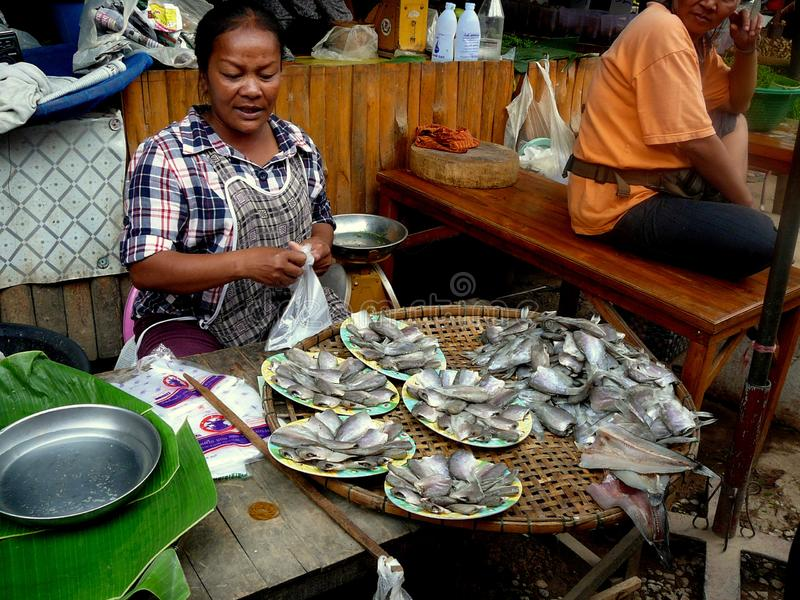 Thailändische Frau, die Fische am früher Morgen-Markt verkauft stockbild