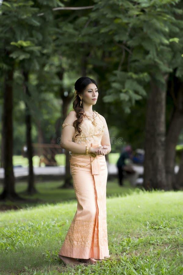 Thailändische Frau, die typisches thailändisches Kleid trägt lizenzfreie stockfotografie