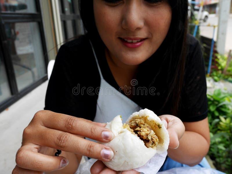 Thailändische Frauenholding und Show Art von chinesischen Imbissen dämpften Materialbrötchen essen vorher an im Freien des Cafés  lizenzfreie stockbilder