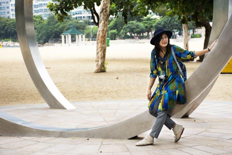 Thailändische Frauenreise der Reisenden und Aufstellung für Nehmenfoto mit Kunstmonument an Repulse Bucht in Hong Kong, China stockfotografie