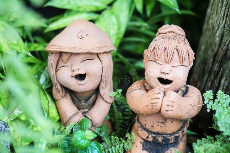Thailändische Gartenlehmsmiley-Mädchenzahl Skulptur lizenzfreies stockfoto