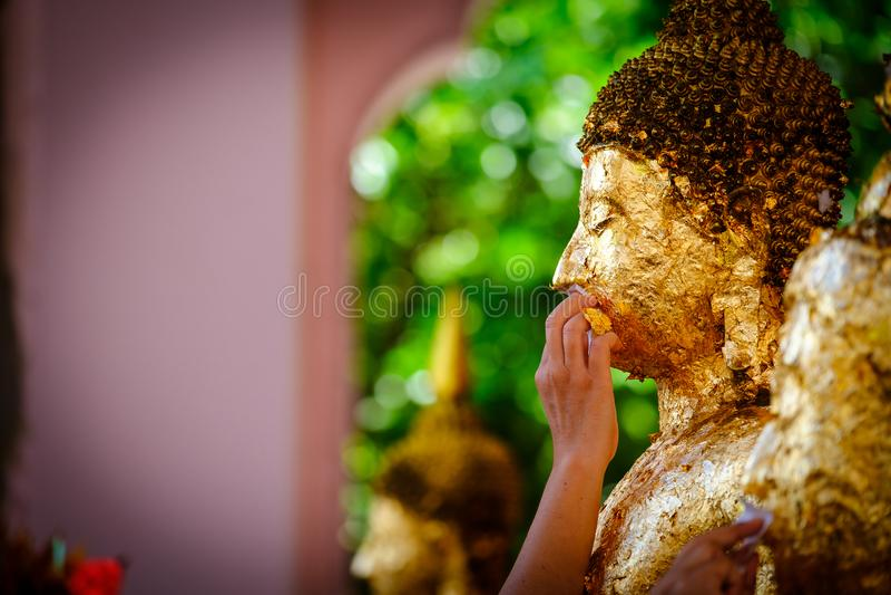 Thailändische Leute machen Verdienst, die Buddhisten, die Goldblatt auf dem Gesicht vergolden stockfoto