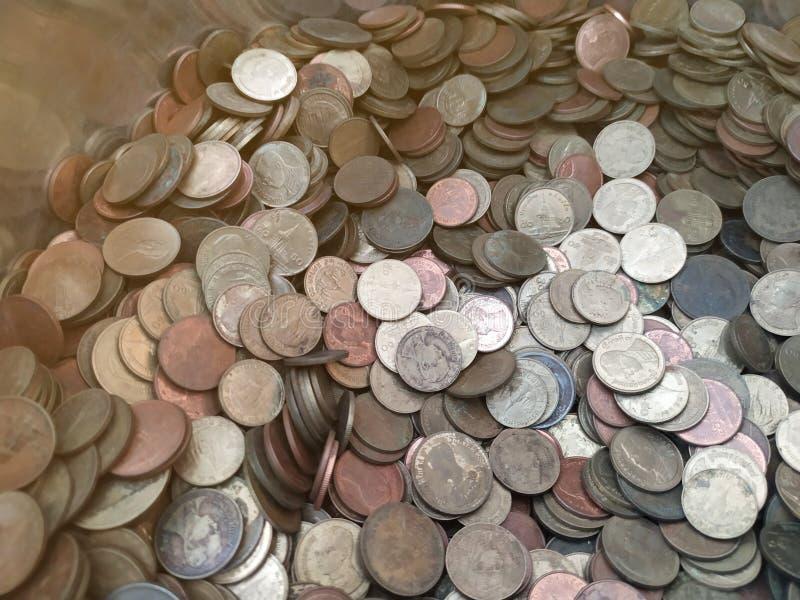 Thailändische Münzen in den Mönchalmosen rollen lizenzfreie stockfotografie