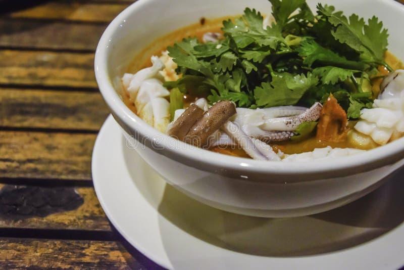 Thailändische Nahrung - würzige Suppengarnierung des Kalmars mit Koriander in der weißen Schüssel auf hölzernem Schreibtisch, kös lizenzfreie stockfotografie