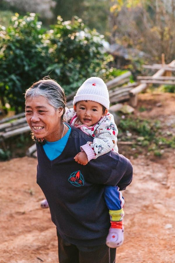 Thailändische Nordgroßmutter, die langärmliges Hemd und ein Kind auf ihr im Akha-Dorf von Maejantai auf dem Hügel zurück tragen t lizenzfreie stockfotos