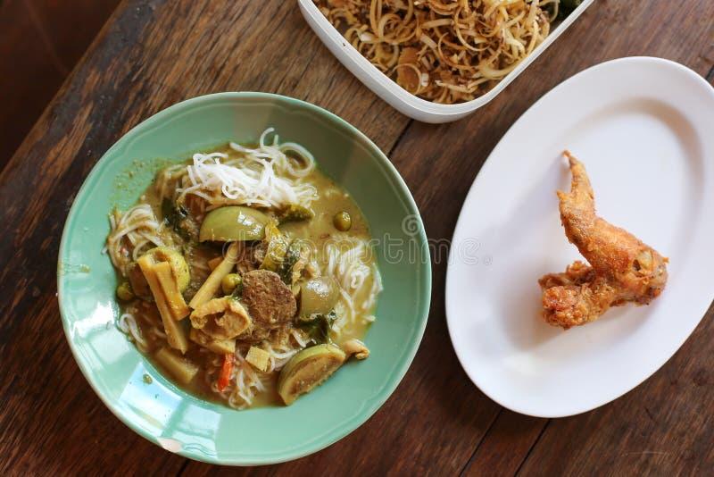 Thailändische Suppennudeln gegessen und Hühnercurry-thailändisches Traditions-Lebensmittel mit Bestandteilen und Kräutern auf höl stockfoto