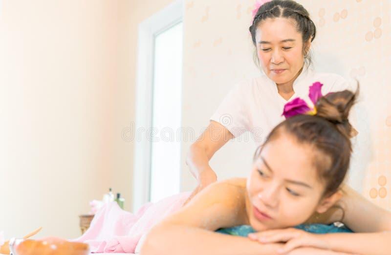 Thailändischer Badekurort-Therapeut, der eine Frauenrückenmassage gibt stockbild