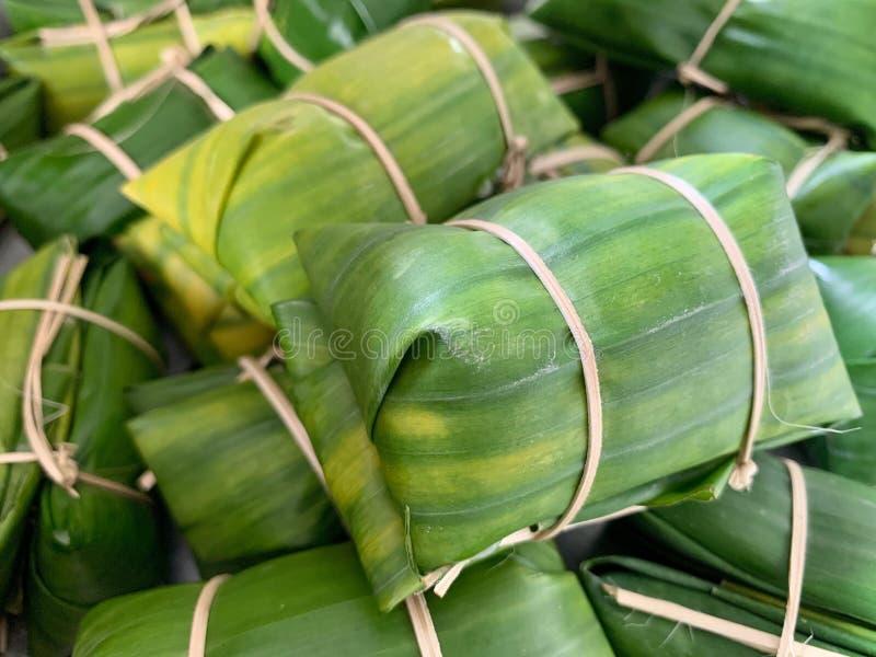 Thailändischer Bonbon mit Reis Banane und Kokosmilch bedeckt durch Bananenblatt und Blutgeschwürstrom oder Khao Tom Mat lizenzfreie stockbilder