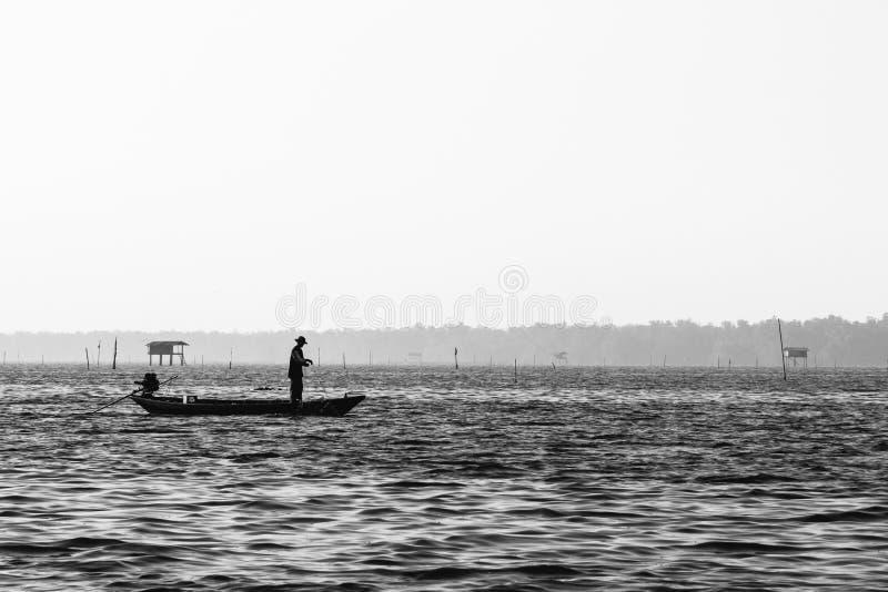 Thailändischer Fischer im Schattenbild Schwarzweiss lizenzfreies stockbild