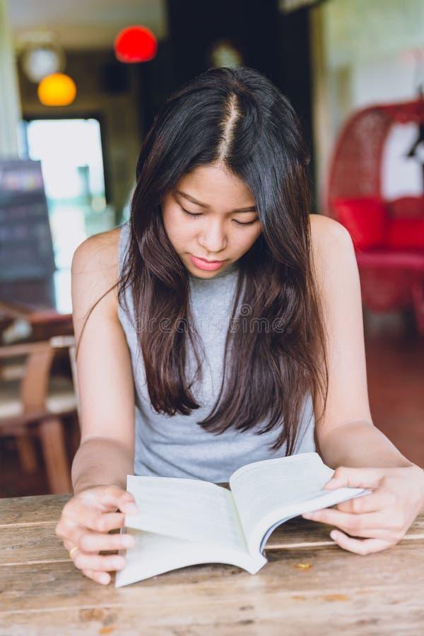 Thailändischer jugendlich ernster Fokus der Asiatinnen, zum des Taschenbuches in der Kaffeestube zu lesen stockfotografie