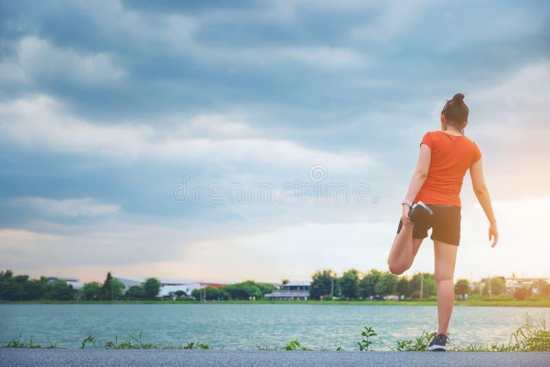 Thailändischer junger Eignungsfrauenläufer, der Beine vor Lauf am Park ausdehnt lizenzfreies stockbild