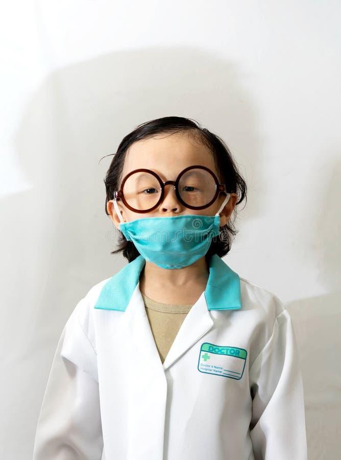 Thailändischer Kinderjunge mit Gläsern in Doktorkleid oder -uniform mit Maskenli lizenzfreies stockfoto