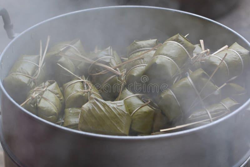 Thailändischer Nachtisch, Banane mit dem klebrigen Reis bedeckt in Bananenblatt khao Tom wütend stockbild