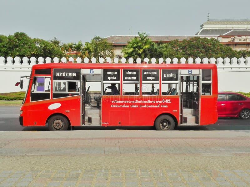 Thailändischer roter Bus am großartigen Palast lizenzfreie stockbilder