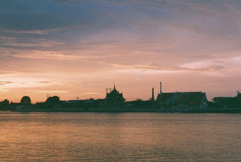 Thailändischer Tempel gelegen nahe bei dem Fluss während des Sonnenuntergangs stockfotos