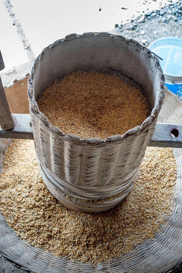 Thailändischer traditioneller Reis, der mit einem hölzernen Mörser und einer Stampfe mahlt Ein alter Reis-Mörser-Paddy am Dorf stockfoto