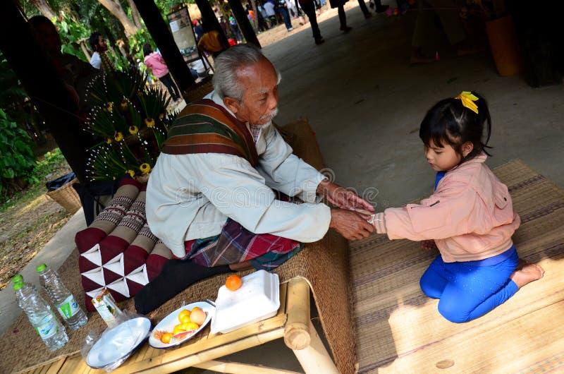 Thailändisches Handgelenk des alten Mannes, das thailändische Segenzeremonie für Hand des Mädchens bindet lizenzfreies stockbild