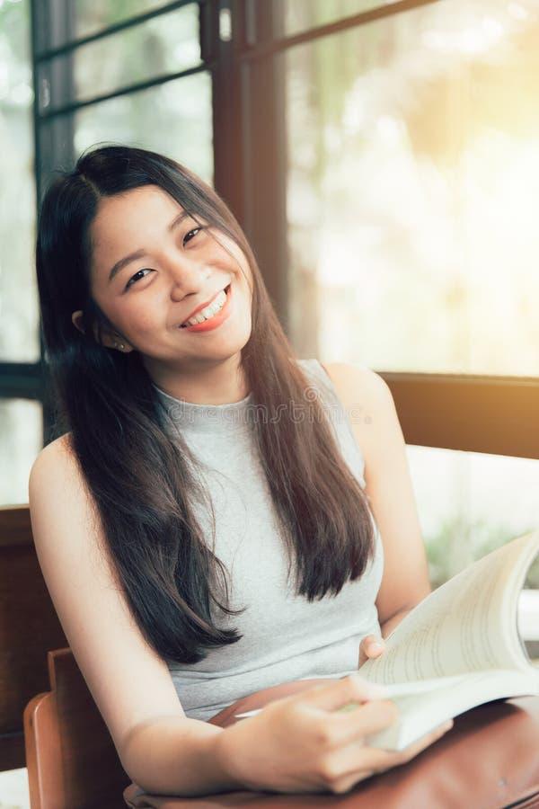 Thailändisches jugendlich Lächeln der Asiatinnen mit Buch im Kaffeestubeweinlese-Farbton stockbilder