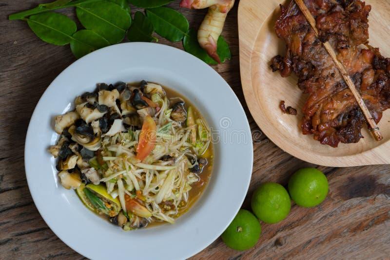 Thailändisches Lebensmittel ` Som-Tam Kai Yang-` oder würziger Salataufschlag der Papaya mit gegrilltem Huhn und Gemüse im hölzer lizenzfreie stockfotos