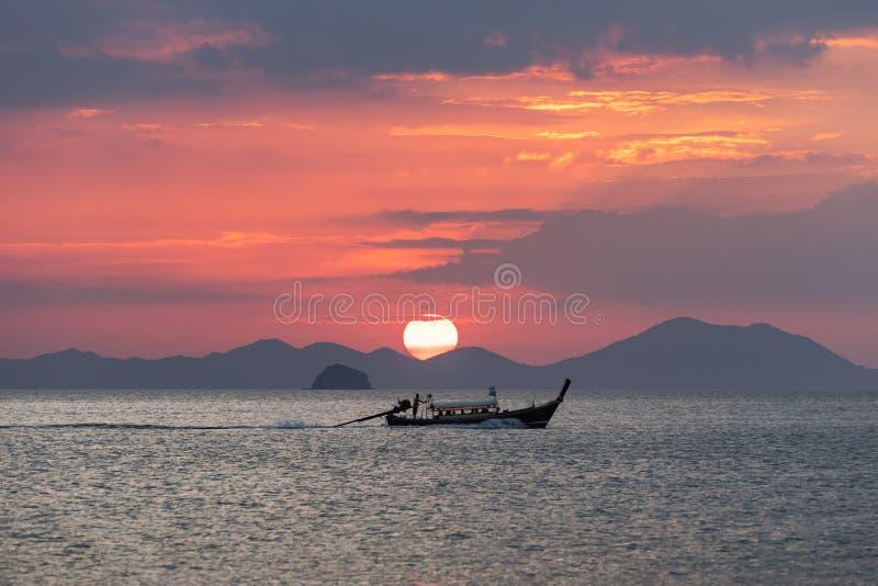 Thailändisches longtail Boot im Meer bei Sonnenuntergang mit großer roter Sonne und Gebirgsschattenbilder und -wolken stockfoto