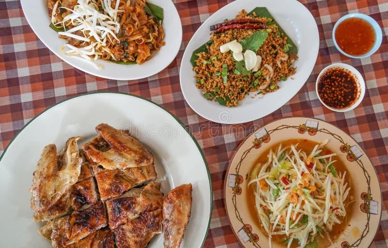 Thailändisches nordöstliches traditionelles Lebensmittel, gegrilltes Huhn, angebratene Nudel, Papayasalat, saure würzige Ente stockfotografie