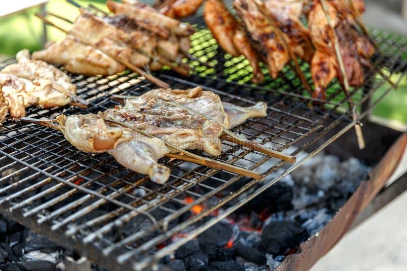Thailändisches Straßen-Lebensmittel: Holzkohle grillte Brathähnchen auf dem halben Schneidölöltank des Ofens lizenzfreie stockfotos