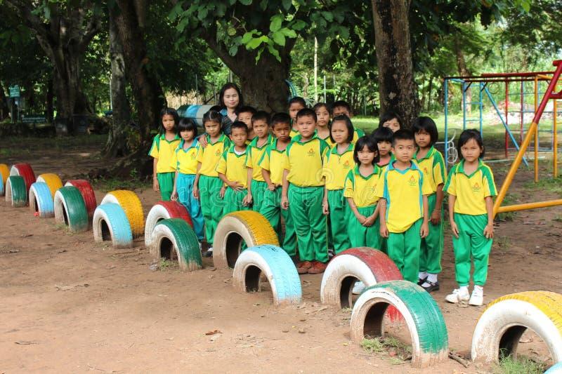 Thailändsk barngrupp och en lärare att posera ett fotografi tillsammans royaltyfri fotografi