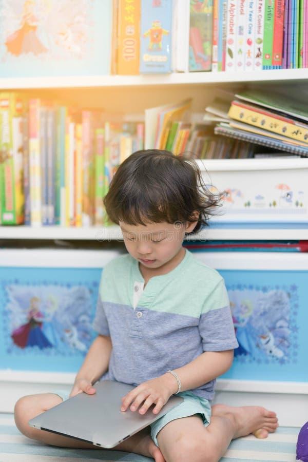 Thailändsk barnpojke som spelar eller läser minnestavlan för studie i rum på bo royaltyfria foton