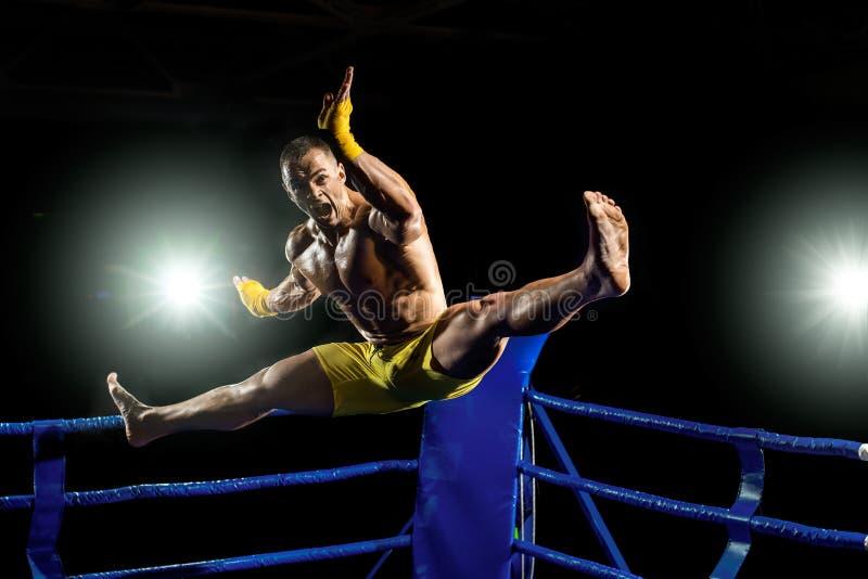 Thailändsk boxare på boxningsringen, hopp och att sparka fotografering för bildbyråer