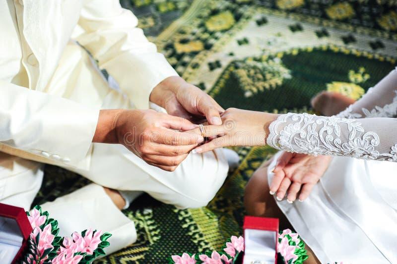 Thailändsk brudgum som sätter en vigselring på hans brud arkivfoton