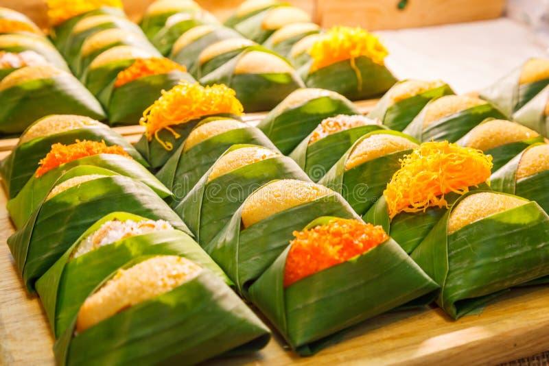 Thailändsk efterrätt: Sött klibbigt ris med ångad äggvaniljsås med toppningvariationer som slås in med bananen, lämnar packen vis fotografering för bildbyråer