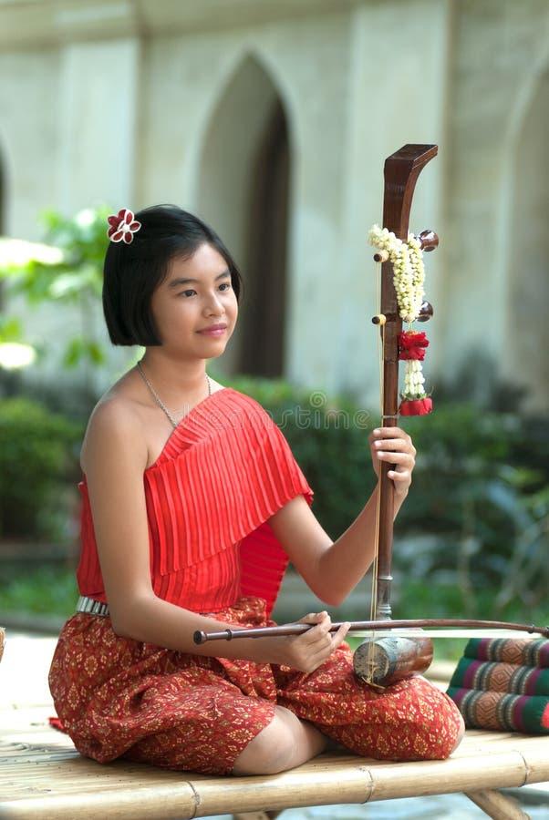 Thailändsk flicka i traditionell klänning, i att spela thailändsk lurendrejeri arkivfoto