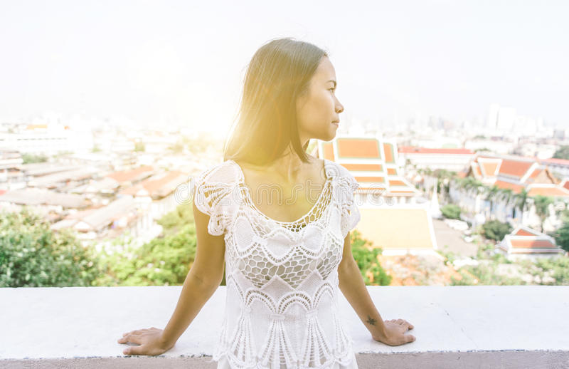 Thailändsk flicka med den vita klänningen på en tempelbalkong arkivfoton
